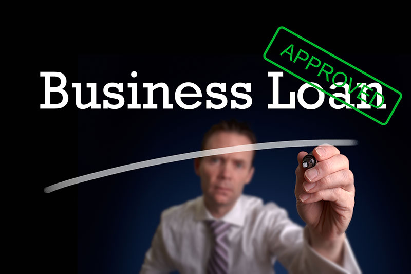Man writing that says Business Loan being approved.