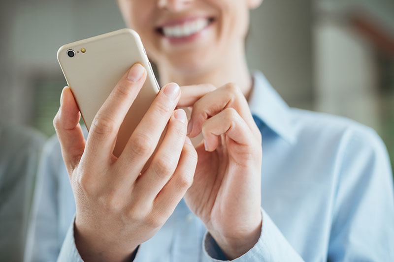 A woman holding a mobile phone and represents the renovating or decorating blog.